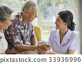 A senior couple is sitting and smiling to a nurse 33936996