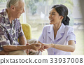 A senior man and a nurse are holding hands and smiling together 33937008