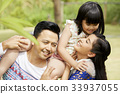 parents are playing with daughter outdoors 33937055