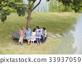 An extended family is sitting and talking together under a tree 33937059