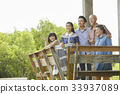 An extended family is standing happily on the balcony. 33937089
