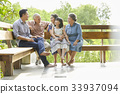 An extended family is sitting, relaxing and having fun on a bench. 33937094