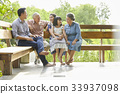 An extended family is talking happily while sitting on the bench. 33937098