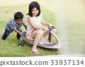a little boy is pushing a toy vehicle with a little girl sitting on it. 33937134