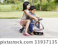 a little boy and a little girl are sitting on a toy vehicle. 33937135