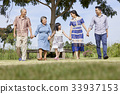 an extended family is holding hands and walking outdoors 33937153