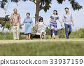 an extended family is walking outdoors and holding hands together 33937159
