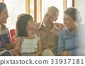 a family of three generation is sitting inside the house and smiling 33937181