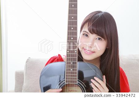 기타를 안고 안고있는 젊은 여성 33942472