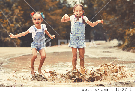 Happy funny sisters twins child girl   jumping on puddles in rubber boots  . 33942719