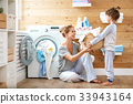 Happy family mother housewife and child   in laundry with washin 33943164