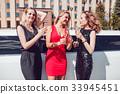 Beautiful women near a limousine drink champagne. 33945451