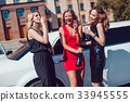 Beautiful women near the limousine have fun and 33945555