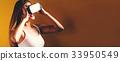 Young woman using virtual reality headset 33950549