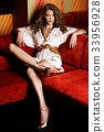 Young, sensual woman sitting on a stylish red sofa 33956928