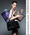 Beautiful naked woman holds fashion handbags 34068364