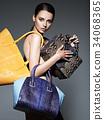 Beautiful naked woman holds fashion handbags 34068365