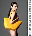 Beautiful naked woman holds fashion handbag 34068368