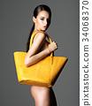 Beautiful naked woman holds fashion handbag 34068370