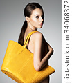 Beautiful naked woman holds fashion handbag 34068372
