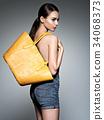 Beautiful naked woman holds fashion handbag 34068373
