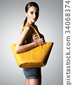 Beautiful naked woman holds fashion handbag 34068374