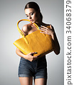 Beautiful naked woman holds fashion handbag 34068379