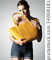 Beautiful naked woman holds fashion handbag 34068381
