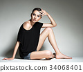 Beautiful woman in black t-shirt and blue shorts. 34068401