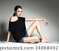 Beautiful woman in black t-shirt and blue shorts. 34068402