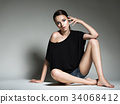 Beautiful woman in black t-shirt and blue shorts. 34068412