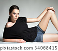 Beautiful woman in black t-shirt and blue shorts. 34068415