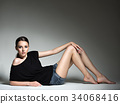 Beautiful woman in black t-shirt and blue shorts. 34068416