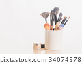 make up brushes in holder and cosmetics isolated 34074578