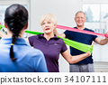Elderly couple in senior gymnastic class doing 34107111