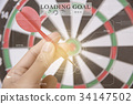 hand holhing red arrow target center of dartboard. 34147502