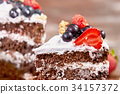 a cut of cake with whipped cream and strawberry 34157372