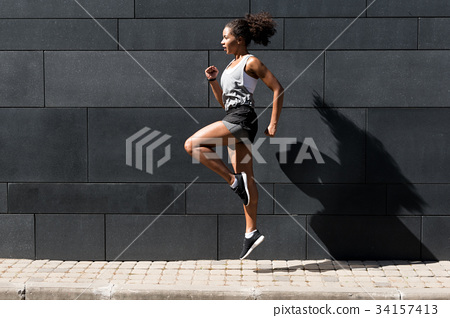 Side view of young woman doing exercising outdoors 34157413