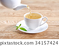 cup with green tea and teapot on white wooden 34157424
