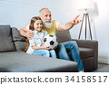 Grandfather and his granddaughter watching 34158517