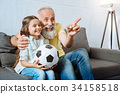Grandfather and granddaughter laughing at funny 34158518