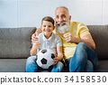 Joyful grandfather and grandson watching football 34158530