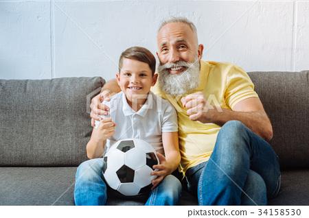 Joyful grandfather and grandson watching football 34158530