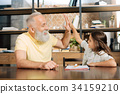 Cheerful little girl giving her grandfather high 34159210