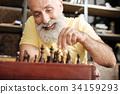 Upbeat senior man playing chess at home 34159293