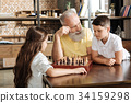 Grandfather giving his grandson a tip in chess 34159298