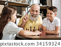 Smiling grandfather having idea about next chess 34159324