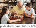 Grandfather suggesting his grandson next chess 34159326