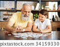 Smiling grandfather and grandson doing a jigsaw 34159330