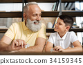 Grandfather and grandson exchanging smiles while 34159345